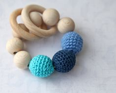 Teething toy with crochet navy blue, cyan/aqua, light pale blue wooden beads and 2 wooden rings. Wooden rattle. Teething ring. $17.00, via Etsy.