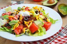 taco salad with big chunks of tomato and avocado