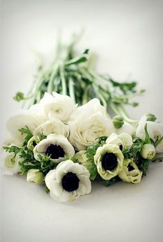 mix of anemones, greenery, and white roses. baby's breath would fit in the mix
