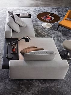 A unique grey sofa with plenty of lay down room that sits atop a soft, darker grey rug in a stylish room designed by Simona Sbordone for Minotti.