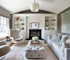 Gray And White Living Room with Tufted Coffee Table containing: Gray Sofa with Pedestal Wingback Chair also Circular Pendant Light plus Curved Ceiling together with Wall Shelving with Round Accent Table also Abstract Wall Art plus Decorative Flower