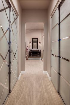 A long hallway with walk-in closets and contemporary sliding doors leads to a glamorous bathroom. Pale wood flooring is paired with taupe walls for a soothing color palette. The bathroom features a glossy floating nightstand, vessel sink and chic modern sconces.