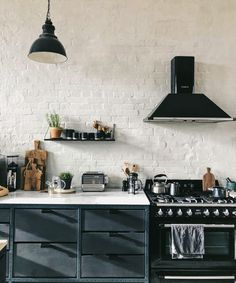 Amazing whitewash brick exposed wall contrasting with dark kitchen cabinets and wooden kitchen accessories in this inspiring kitchen Minimal Kitchen Design, Kitchen Lighting Design, Kitchen Lighting Fixtures, Light Fixtures, Wooden Kitchen, Rustic Kitchen, Kitchen Dining, Kitchen Decor, Kitchen Ideas
