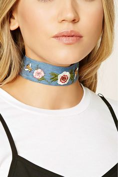 A denim choker featuring a floral and bee embroidery, high-polish accents, and a lobster clasp closure.