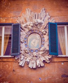 A maddonelle, a shrine to The Virgin Mary on the outside of a building.  The frame is accented by putti, the lovely sculptured cherubs.
