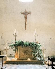 Trailing greenery and plenty of pillar candles adorned the altar of the intimate…