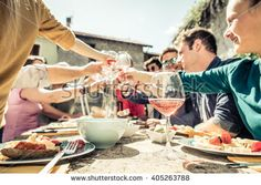 Group of friends toasting wine glasses and having fun outdoors - People having…