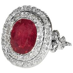 Edwardian Burmese Ruby Diamond Platinum Ring. An Antique English Burmese Ruby platinum ring surrounded by two rows of diamonds. The center oval cut Burmese ruby weighs 5.26 carats. The ring is decorated with diamond Edwardian garland bows flanking the center cluster. American Gemological Association certificate CS41856 states that the ruby is of Burmese origin, with no indications of heating. Circa 1905.
