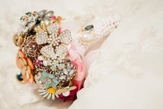Brooch Bouquet. half a Styrofoam ball covered in fabric and tulle. Brooches from Grandmothers. Put flower wire on brooches and push through styrofoam ball. base can be bought at Michaels and covered in ribbon and string of fake pearl beading.
