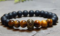 About the Bracelet This mens black onyx bracelet features a brass lion representing the lion spirit of courage and strength. Bracelet Details: This mens bracelet is made with: - 8mm Black Onyx - Brass