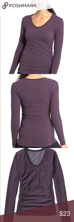 Athleta Dottie Pure Top Deep V-neck front. Shirred front and back panels double as Tummy camouflage. Fitted. Fits next to the skin. Made of Cotton/Nylon/Spandex. Color is Wild Raisin. Size is XL. Athleta Tops