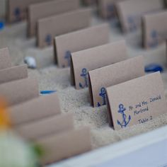 The couple stamped the escort cards with an anchor -- Kim's bridesmaid handwrote guests's names. Each one was placed in a bed of sand.  from the album: A Nautical Wedding in Mashpee, MA