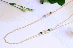 Long necklace for women with gold flowers and emerald green glass.