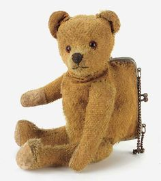 A Teddy Bear purse with golden mohair, orange and black glass eyes, pronounced muzzle, black stitched nose and mouth, swivel head, jointed limbs with felt pads and metal framed purse in back with chain handle 9½in. high, 1920's.