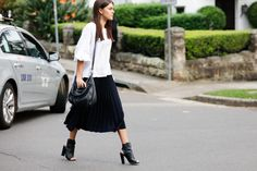 A white blouse is worn with a black pleated midi skirt, a black cross body bag and peeptoe ankle boots