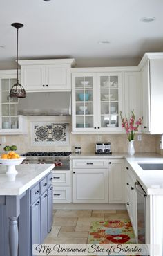 White and Grey Elegant Kitchen remodel.  They mixed creamy cabinets with a grey center island all in warm colors.  Travertine floors and back splash with a quartzite countertop.