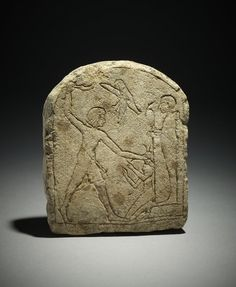 Small round-topped limestone stela depicting a king smiting a kneeling figure before Ptah. XVIIIth dynasty. Memphis - Mit Rahina. British Museum.