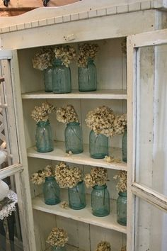 love this cabinet and all the flowers in mason jars