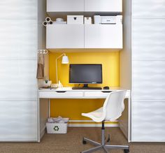 White IKEA chair on castors in front of a workspace between two wardrobes.
