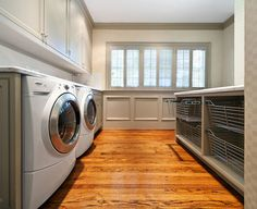 Laundry Room Ideas. Huge laundry room with white washer & dryer, gray cabinets, gray painted wainscoting, gray laundry island and wire bins....