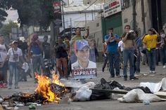 Demonstrators, one holding a poster of opposition presidential candidate Henrique Capriles, confront riot police from behind a burning barricade in the Altamira neighborhood in Caracas, Venezuela