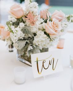 Beautiful flower centerpiece with gold-lettered table number,  white hydrangea, blush/pink roses, and dusty miller. Willowdale Estate, a weddings and events venue north of Boston, Massachusetts. WillowdaleEstate.com | Lena Mirisola Photography  |  Petals Inc.