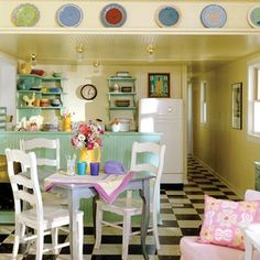 Lake Trailer Cottage ~ completely transformed with checkerboard flooring, beaded board walls, vintage refrigerator, and turquoise kitchen underscore the '40s feel of the home. Simple open shelving to show off colorful collectibles and new Fiestaware.
