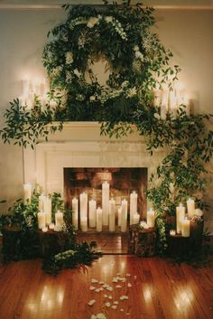Greenery with baby's breath accents and tall pillar candles create this stunning ceremony backdrop