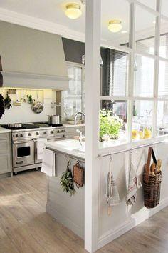 Une cuisine blanche semi-ouverte avec une verrière interieure