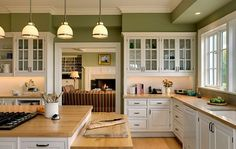 green painted cabinets | white kitchen cabinetry with wooden furnishings and green walls