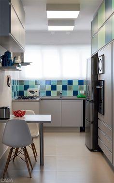 Mosaico de azuis. Azulejos de 15 x 15 cm, comprados num depósito de revestimentos, colorem a bancada. As mesmas cores surgem no laminado texturizado da área superior do armário. Piso da Portobello.