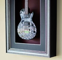 Frame your most prized possession. JOANN can custom frame nearly everything. A shadow box can be created to display and hold even a guitar, with no glass here to allow for removal and use.