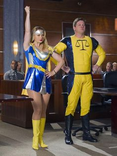 Kim Kaswell and Owen French in superhero costumes in court. Drop Dead Diva