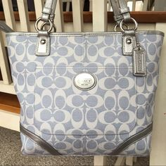 COACH Medium Blue Silver Signature PVC Tote  Beautiful, COACH, light blue with silver, PVC signature tote.  Purse has zip closure, one outside slip pocket,  And two inside slip and one inside zip pocket.  Good pre-loved condition.  Very minor signs of wear.  11 X 11 X 3.  Strap drop 9 inches. Coach Bags Totes