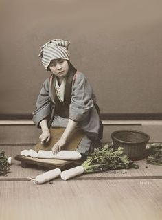Young woman wearing a grey kimono and blue and white striped head scarf, cutting up daikon radishes.  About 1900, Japan.  Text and image MIA