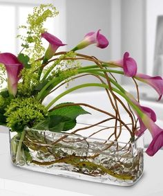Sleek and elegant pink calla lilies are cascading over this rectangular vase filled with gem stones. Created by Beneva Flowers, Sarasota Florist