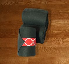 """Equine Polo Wraps/Gray Polo Wraps w/Red Quatrefoil Velcro Strap by KLMequestrian Deck out your horse in style with these gray polos made with quality gray fleece embellished with red quatrefoil fabric on the velcro strap. Made with industrial strength velcro to ensure a proper hold.  Three sizes offered: Pony: 2 yards (6ft) length, 4"""" wide  Horse: 9 ft front, 11 ft hind length, 5"""" wide Extra Long: 4 Yards (12 ft) length, 5"""" wide"""