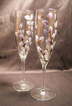 Glasses hand painted featuring softly lavender frosted pussy willow 'catkins' on platinum branches or frosted on gold branches. A classic harbinger of spring these toasting flutes are most often displayed during the Lunar New Year as decoration to represent the coming of prosperity. 9 inch height each individually and delightfully designed by hand and delightfully. Your pair will be Uniquely Yours within this design. MADE TO ORDER processes within 5 to 7 business days prior to shipping. I…