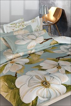 An engineered design with branches of oversized, softly textured magnolia blossoms and lush green leaves on a textured blue background. Reverses and coordinates with an all-over print of small magnolias on a bright white background. Linen Pillows, Linen Bedding, Bright White Background, Beige Bed Linen, Bed Styling, Lush Green, Blue Backgrounds, Shades Of Blue, Printing On Fabric