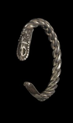 BALTIC VIKING SILVER PLAITED BRACELET Circa 9th-11th century AD. A c-shaped bracelet formed from three silver rods plaited into a triangular-section hoop, with traces of additional filigree wire between; the terminal formed as a flat plate with hollow piriform raised bulb with pelletted border; the bulb with T-shaped pelletted strap and granule rosette, the other terminal mostly lost in antiquity. Silver,