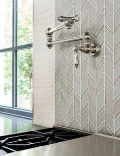 Chic kitchen features a swing-arm pot filler lining a gray and blue glass chevron tiled backsplash placed over a gas cooktop. Chevron Kitchen, Chevron Tile, Herringbone Tile, Gray Chevron, Glass Backsplash Kitchen, Backsplash Tile, Backsplash Ideas, Pot Filler Faucet, Stools For Kitchen Island