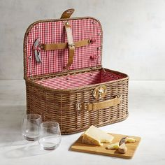 Have picnic basket, will travel. The rich honey-brown finish of our suitcase-style basket sets the tone for a classic outdoor excursion. Hand-woven of synthetic wicker, it opens to reveal a fun gingham interior and bonded leather straps. It's perfect for holding your glassware, bamboo cheese board and stainless steel utensils. Plus, it's a cinch to carry, so you can dine <i>al fresco</i> wherever your journey takes you.