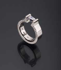 Hard Omega (HO) with Side Channel shown in Platinum featuring an Emerald-cut center stone