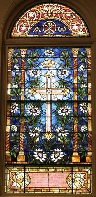 Stained glass original Tiffany cross with lilies. Window restored by Phoenix Studio.
