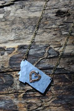 """This necklace simply says there's no place like home. DETAILS The hammered aluminum Montana pendant is approximately 1 1/2"""" wide and hangs from an 18"""" antique brass chain. A gorgeous antique brass hea"""