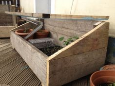 Garden cold frame for plants with clear acrylic hinged lid.