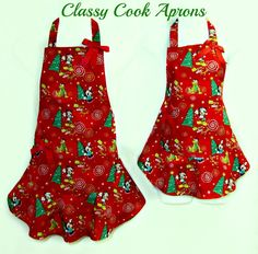 How cute are these?!! Darling Mommy & Me Apron Set in a Disney Character Christmas screen print featuring Mickey, Minnie and Pluto trimming trees, entitled 'Merry & Bright'. For a touch of panache, we added ruffled feminine flounces, perfectly matched and lined right hand pockets, and a pair of Red grosgrain bows. Just two girls in the kitchen....cooking, baking and candy making for the Holidays! Minnie Mouse Christmas, Mickey Mouse, Cute Kitchen, Kitchen Ideas, Disney Kitchen, Sewing Aprons, Apron Designs, Two Girls, Merry And Bright
