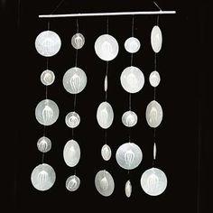 Capiz is een platte, oesterachtige schelp, die in grote hoeveelheden voorkomt in de wateren rond de Filippijnse eilanden. De schoongemaakte schelpen worden in de gewenste vorm gesneden en in elkaar gezet middels soldering in een familiebedrijf. En het wordt aan elkaar genaaid met nylon draad in een ander familiebedrijf. Resultaat: een mooie mobiel! Price € 10,95