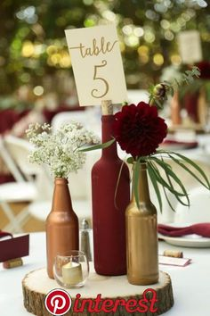 Gold and burgundy wine bottle centerpiece on wood round- decor idea from vineyard wedding from Gale Vineyards in California winecountryweddings VineyardWedding winerywedding galevineyards Wine Bottle Centerpieces, Wedding Wine Bottles, Wedding Table Centerpieces, Flower Centerpieces, Centerpiece Ideas, Diy Wedding Table Decorations, Wedding Jars, Simple Centerpieces, Beer Bottles