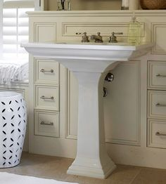 The one strike against installing a pedestal sink in a small bath is limited storage space. By adding a tall, skinny cabinet behind the sink, you can have the best of both worlds: convenient compartments for beauty products and a streamlined sink that won't weigh your bath down.